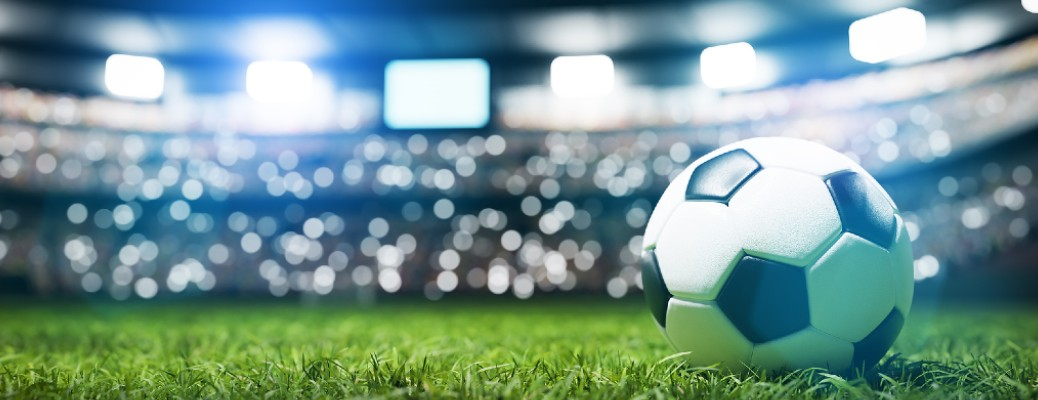 A soccer ball sitting on grass in a stadium with fans in the background