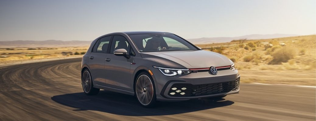A grey-colored 2022 Volkswagen Golf GTI driving in the desert