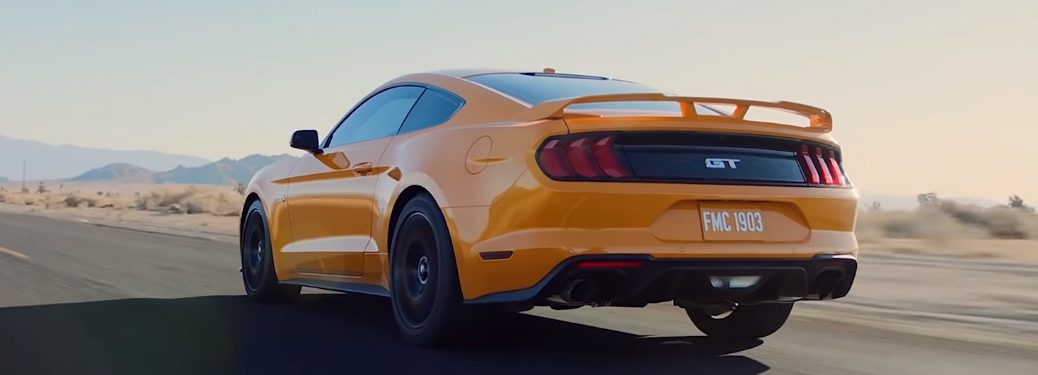 Yellow 2019 Ford Mustang driving on a desert highway