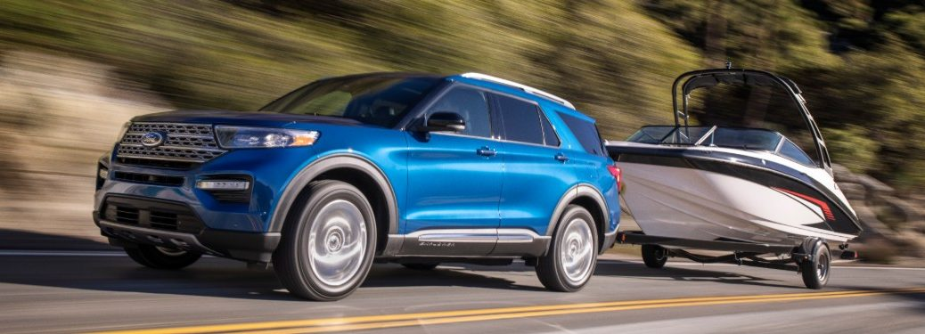 Front driver angle of a blue 2020 Ford Explorer Hybrid towing a trailer