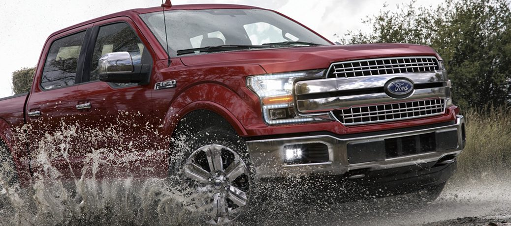 Red 2020 Ford F-150 plows through muddy water