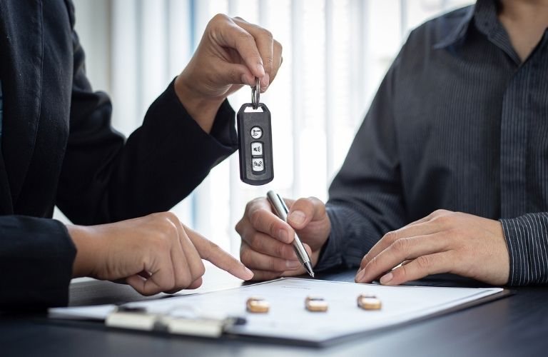 Car keys in hand and signing the loan agreement