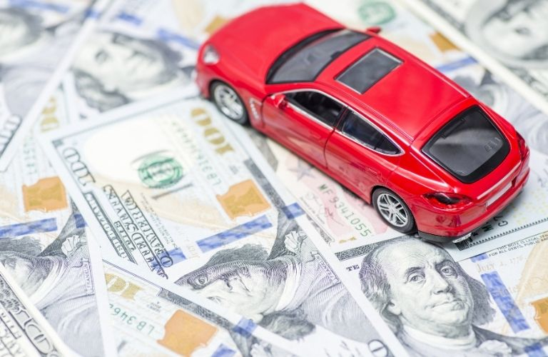 Red toy car and dollar bills