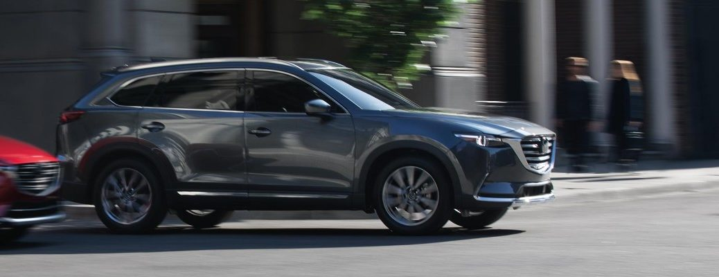 2019 Mazda CX-9 exterior side shot with gray paint color driving through a city