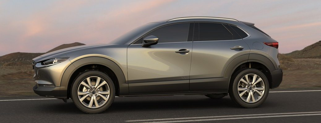 2020 Mazda CX-30 exterior shot driver side gray paint facing right at twilight on a road