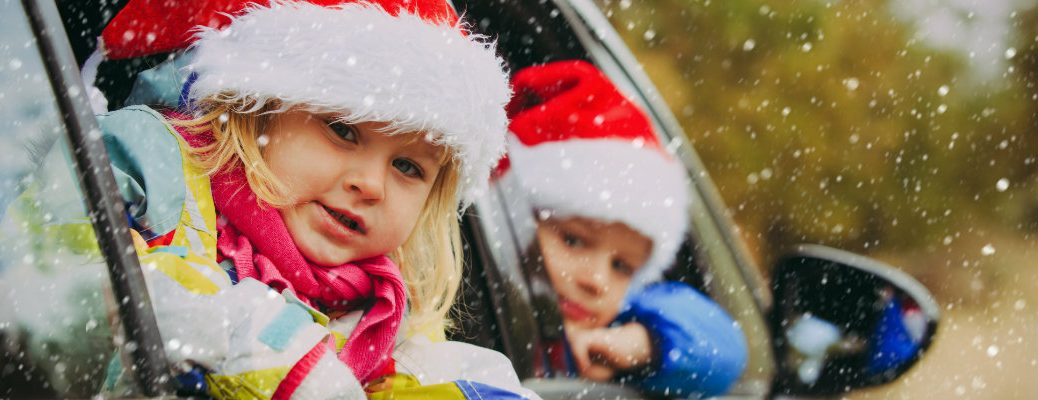 Kids in a vehicle wearing Santa hats