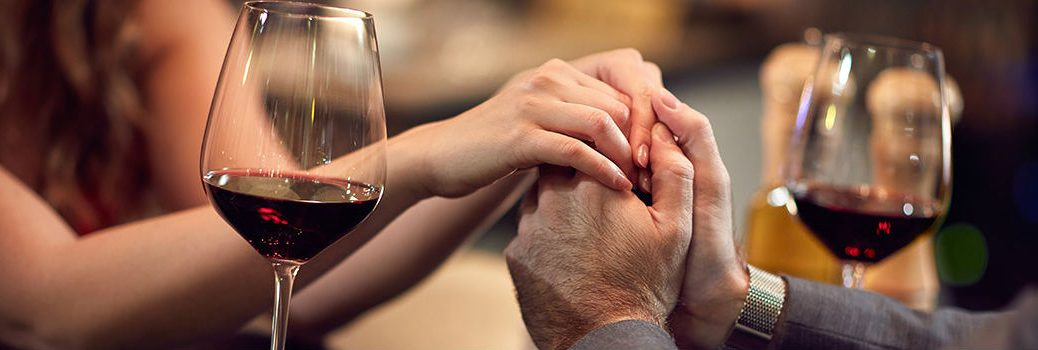 couple holding hands at a dinner table