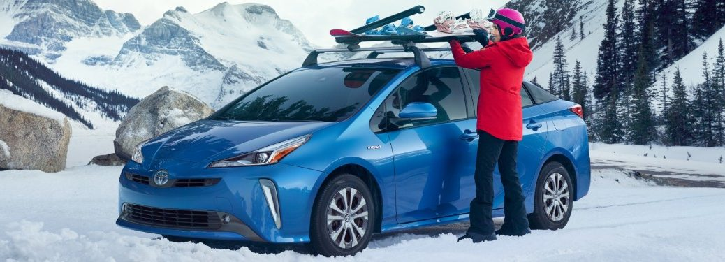 Woman pulling snowboards off the top of a blue 2019 Toyota Prius in a snowy and mountainous area