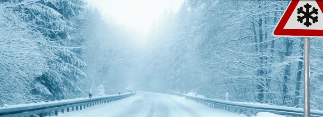 Snow covered roads with a sign showing a snowflake