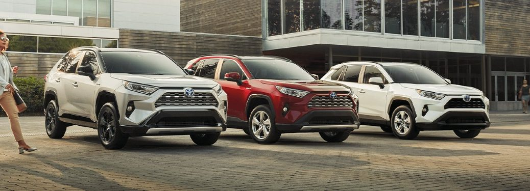Three 2020 RAV4 hyrbids lined up outside of modernist house