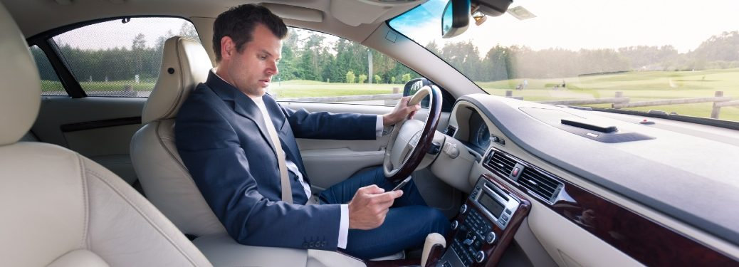 man texting while driving in a upscale car