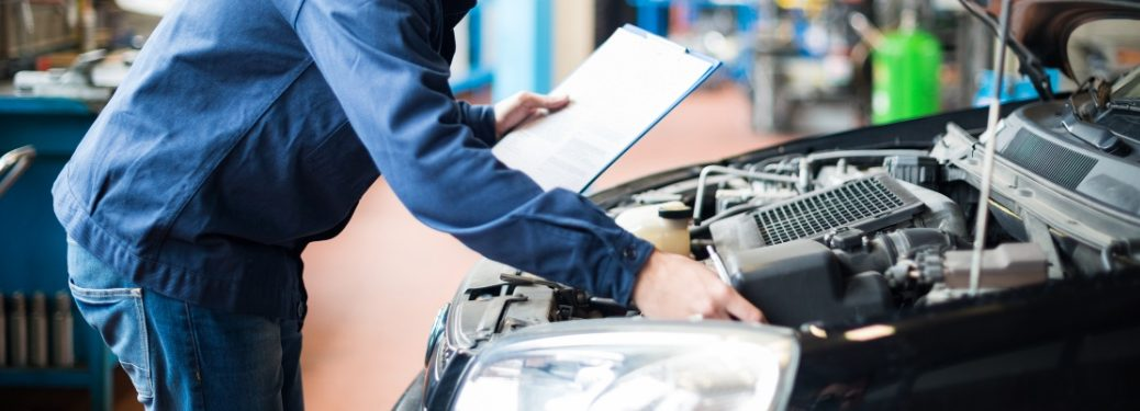 mechanic with clipboard doing inspection on car