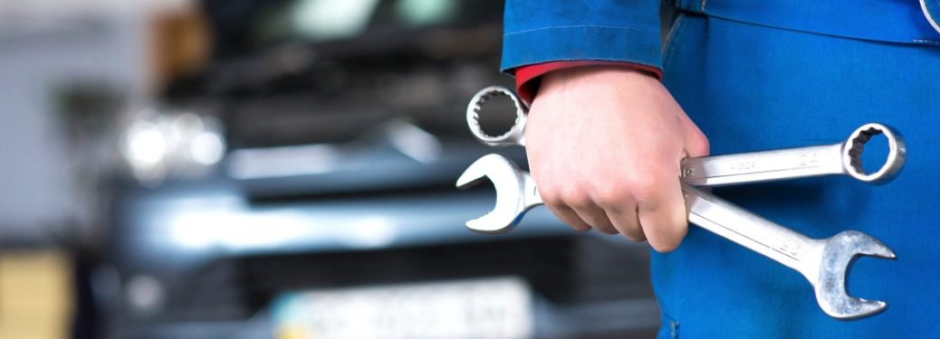 mechanic holding wrenches in front of vehicle