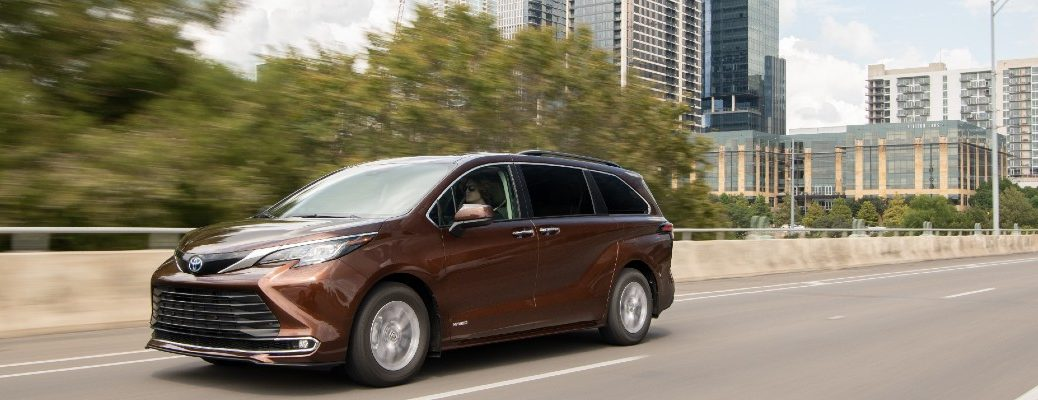 A front left quarter photo of the 2021 Toyota Sienna on the road.