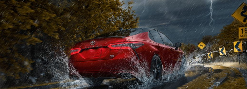 2021 Toyota Camry driving down a rural road in a storm