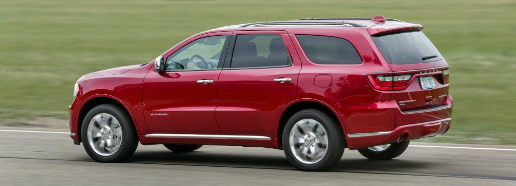 left side view of red dodge durango driving