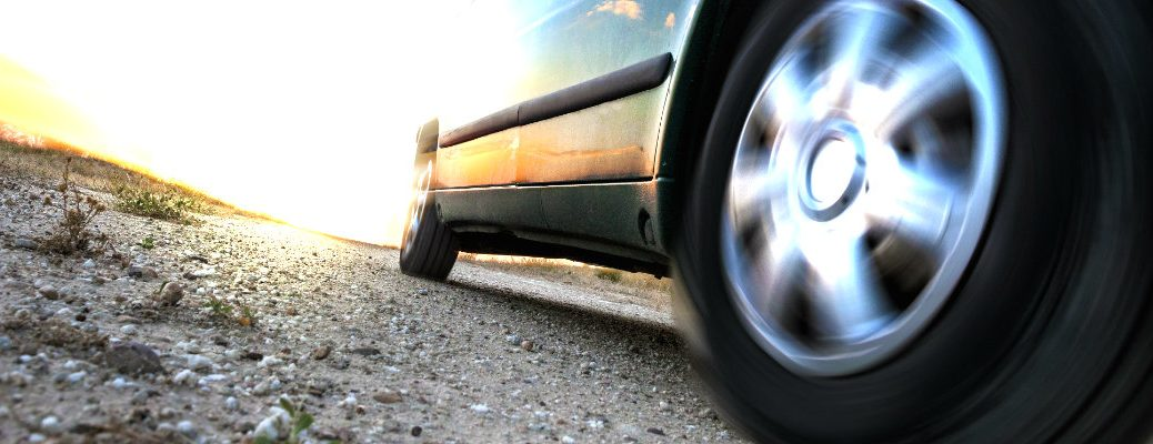 Low-angle photo of a vehicle's wheel and tire