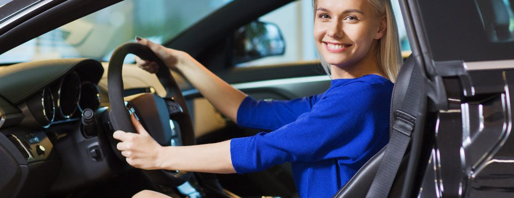 Woman in blue dress behind the wheel of a new vehicle