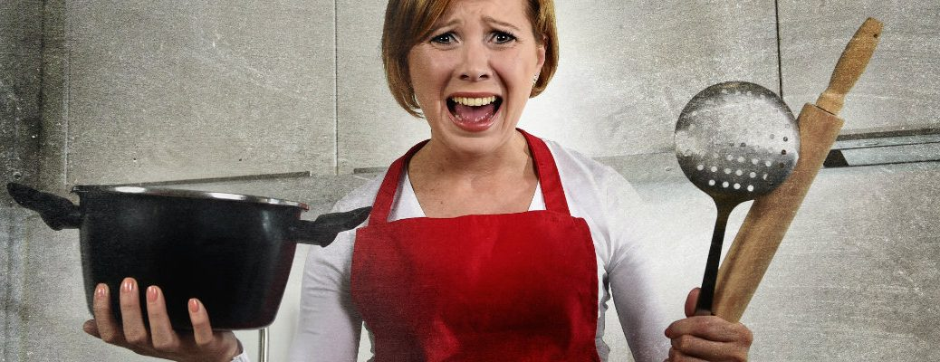 Woman in a kitchen wearing a red apron