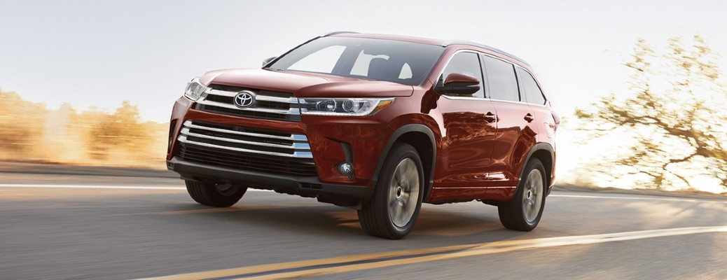 A red 2018 Toyota Highlander driving down an open road.
