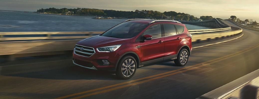 A red 2017 Ford Escape with a turbocharged engine driving down an open road.