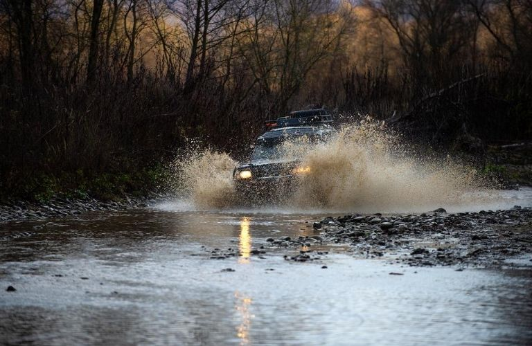 Vehicle driving through water and mud