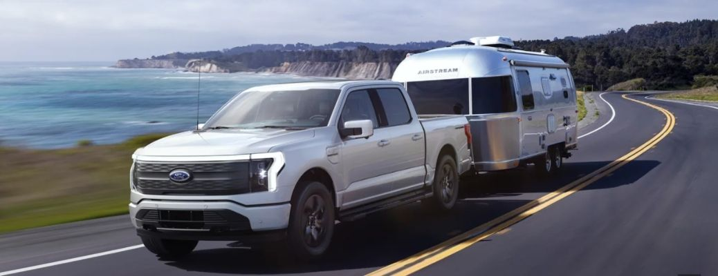 2022 Ford F-150 Lightning driving with trailer