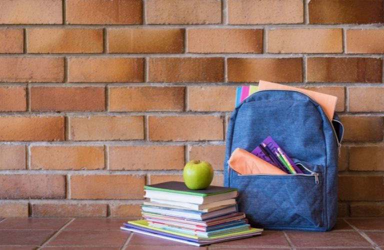 A school bag with a stack books and an apple
