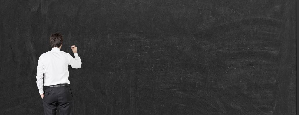 A man standing in front of a black board