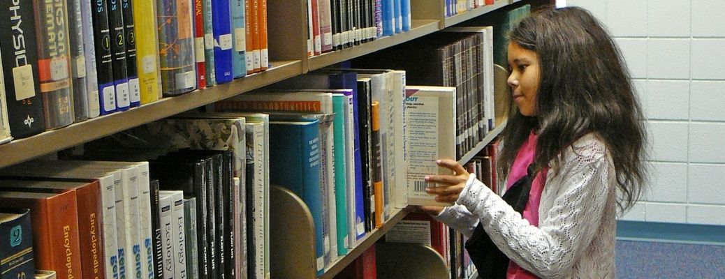 A girl taking a book out of a shelf in a library.