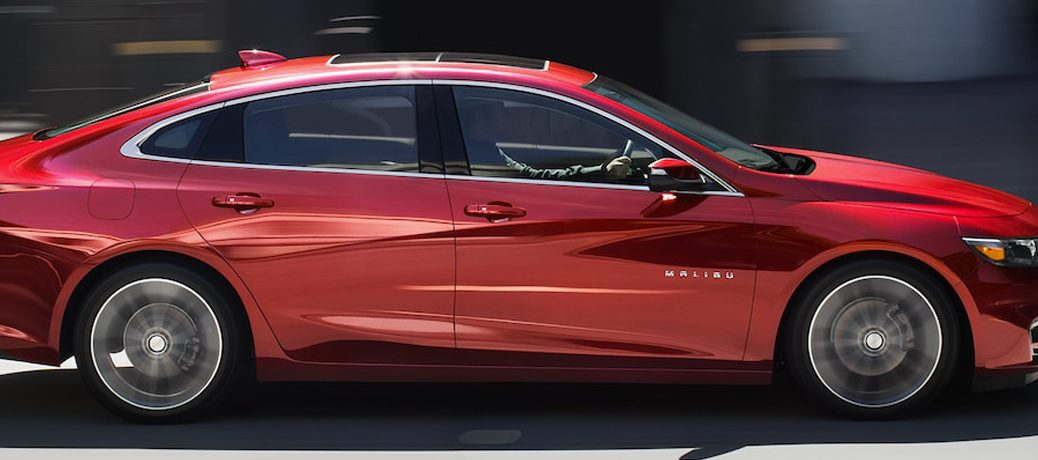 Exterior View Of A Red 2018 Chevrolet Malibu Driving Down City Street During The Day