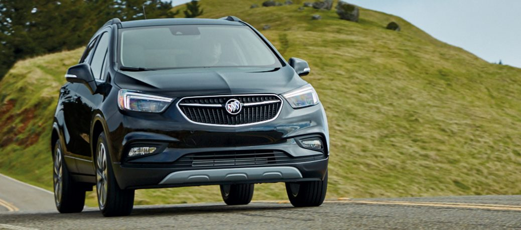 Exterior View Of A Silver 2019 Buick Encore Driving Down Country Road