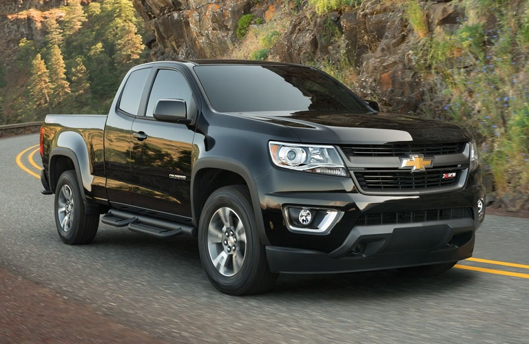 Exterior View Of A Black 2019 Chevrolet Colorado Driving Down Two Lane Road