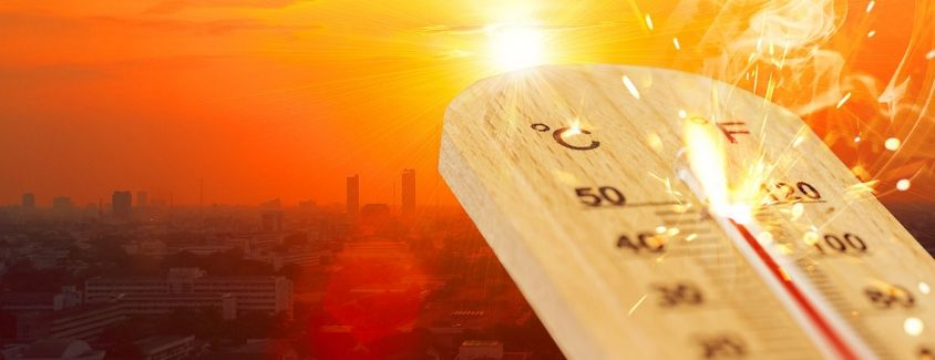 Image of a thermometer showing the hot temperature in the city in the background