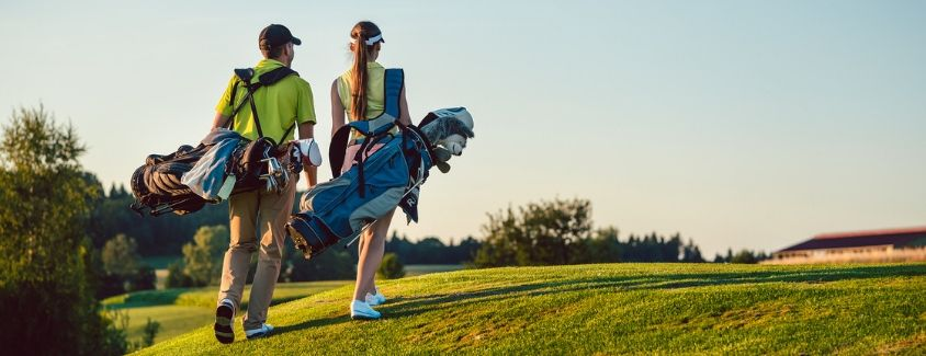 Image of a man and a woman walking on a golf course