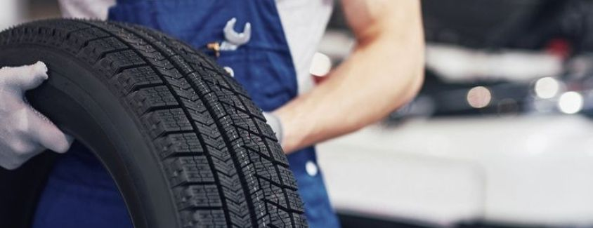 Image of a service technician holding a new tire