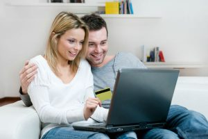Young couple holding a laptop shopping for a new car on a couch