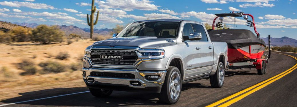 2019 Ram 1500 driving on a road towing a boat