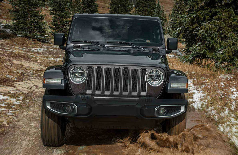 2019 Jeep Wrangler driving on a muddy trail