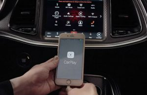 An iPhone being paired to Apple CarPlay on a Dodge vehicle