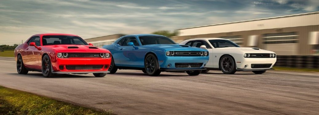 Three 2020 Dodge Challenger muscle cars driving next to each other