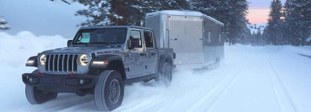 2021 Jeep Gladiator towing a trailer on a snow covered road