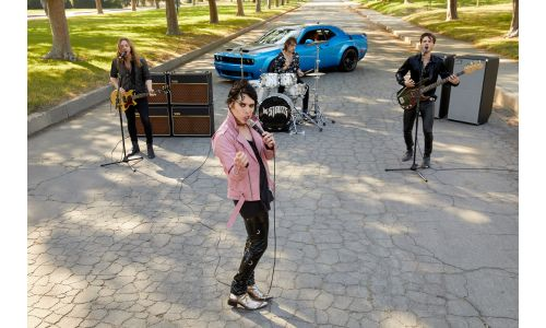 The Struts performing Dancing in the Street in the middle of a suburban road with a 2019 Dodge Challenger model parked behind them