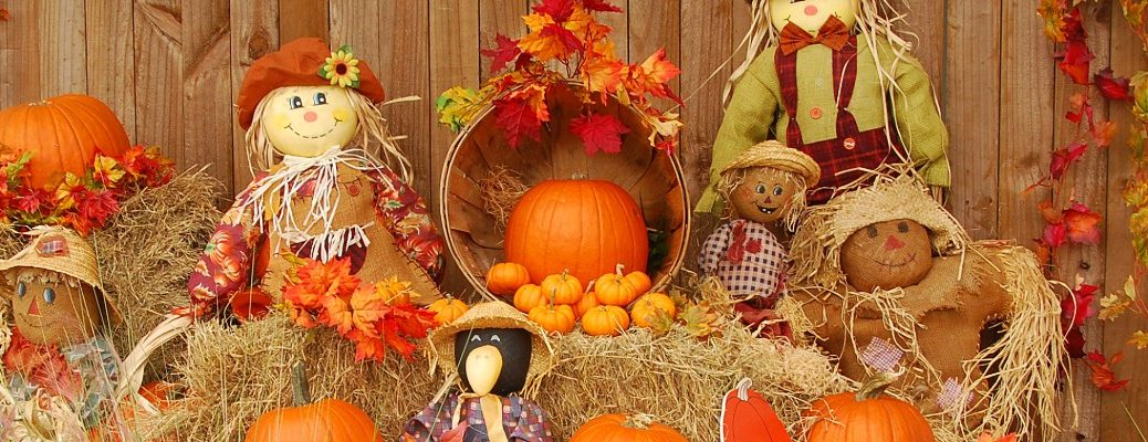 a bunch of tiny scarecrows, pumpkins, and fall leaves sitting atop bales of hay near a decorated wooden fence of a pumpkin patch