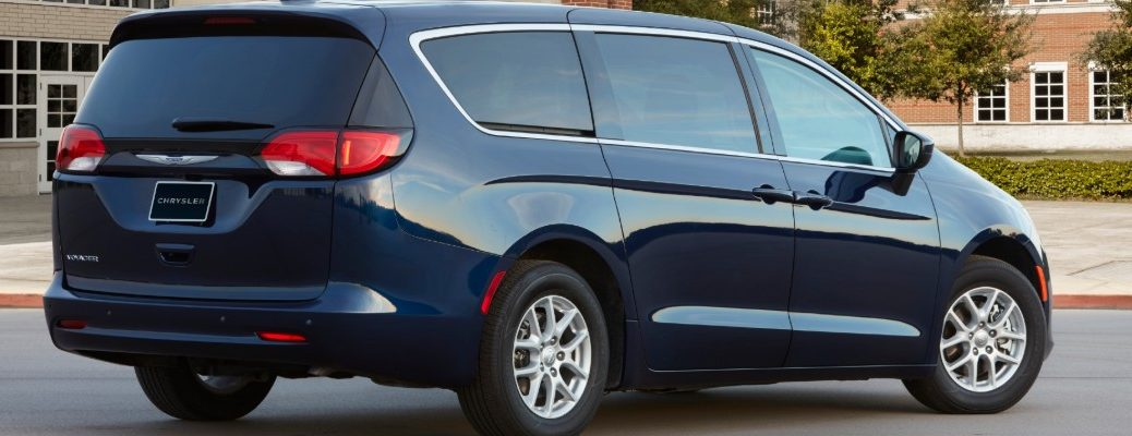 2020 Chrysler Voyager minivan exterior rear shot with jazz blue paint color parked outside a fancy brick university campus