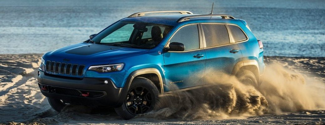 2020 Jeep Cherokee exterior side shot with Hydro Blue Pearl Coat paint color driving on a beach as it kicks up sand with an ocean wave background