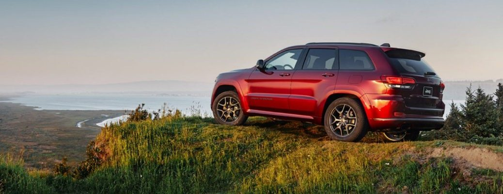 2020 Jeep Grand Cherokee exterior side shot with Velvet Red paint color parked on a grassy hill cliff overlook mountains and a lake