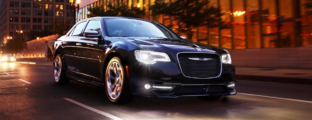2020 Chrysler 300 luxury sedan exterior shot with Gloss Black paint color driving through a city at night with LED headlights on