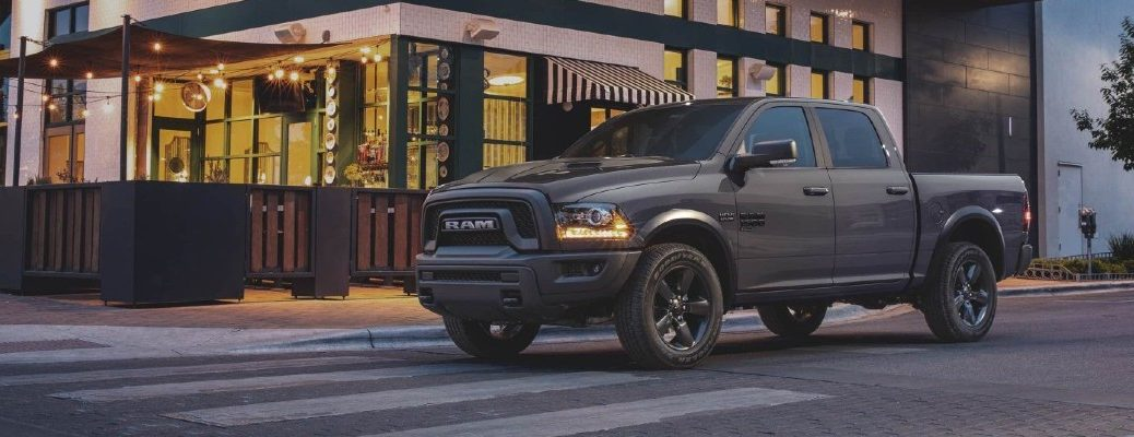 2020 Ram 1500 Classic pickup truck Warlock trim level exterior shot with gray brown paint color parked outside a restaurant at a crosswalk