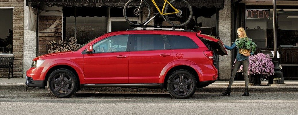 2020 Dodge Journey exterior side shot with Redline paint color as a woman opens the trunk to load in flowers and pots